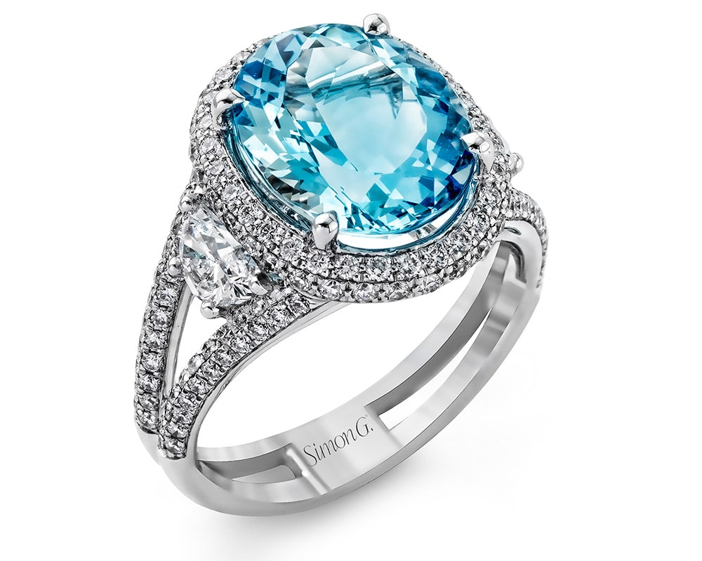 Ladies 18kt White Gold Oval Halo Split Shank Fashion Ring with Blue Zircon Center Stone